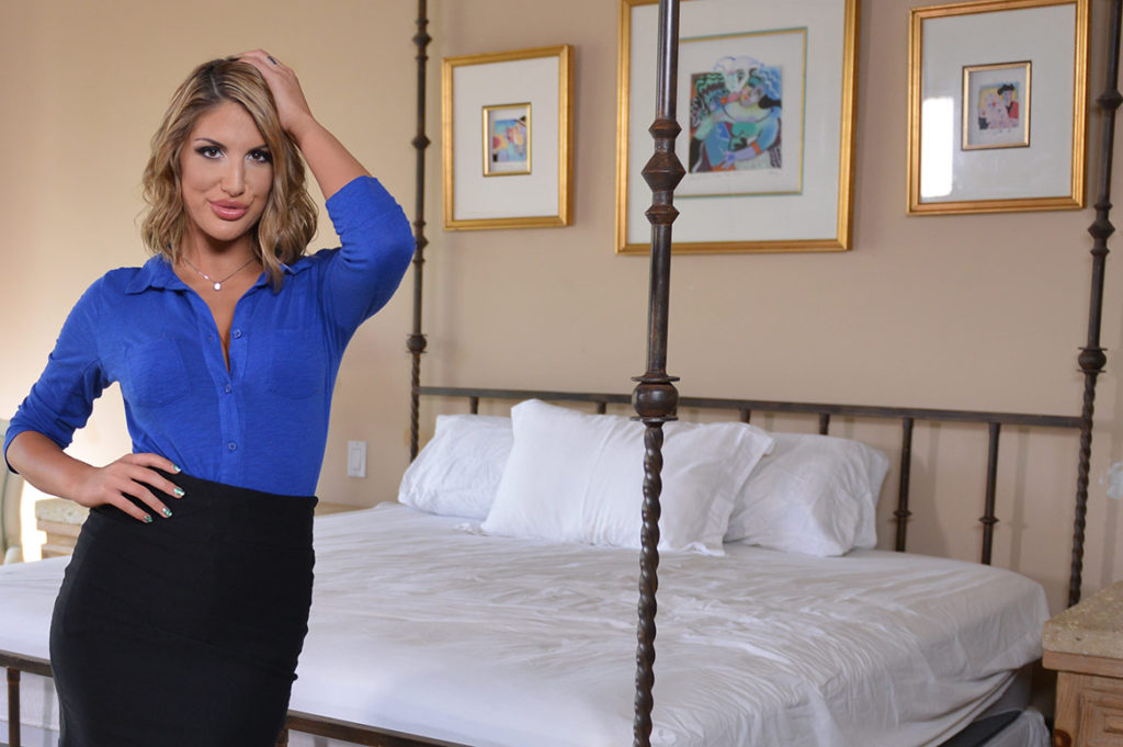 Porn star in bedroom standing beside four-post bed