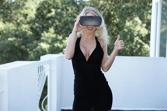 Katie Morgan, wearing a pair of Gear VR goggles, gives the thumbs up to VR porn.