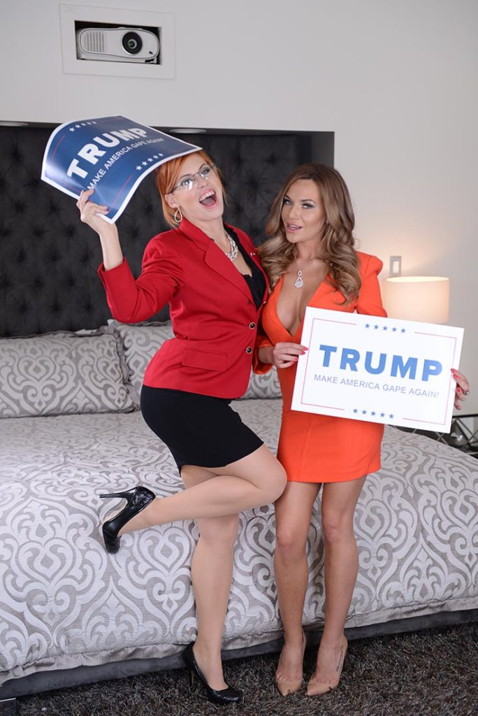 Porn stars playing Melania Trump and Sarah Palin hold campaign posters that read Make America Gape Again