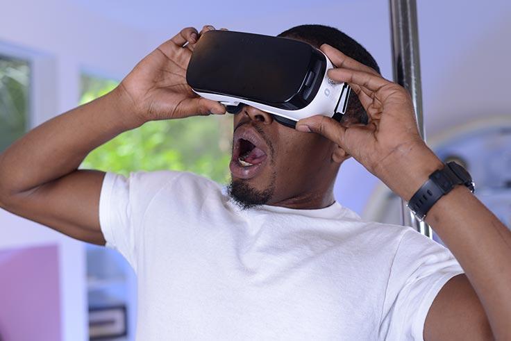 Black man in bedroom wearing Gear VR hedset, looking shocked at what he sees
